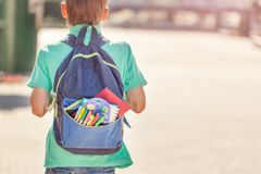 Schoolboy with full backpack go to school. Back view.  stock image