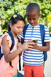 Schoolboy and girl using mobile phone at campus Royalty Free Stock Photography