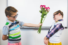 Schoolboy giving a bunch of flowers to a girl in classroom Stock Image