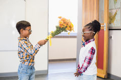 Schoolboy giving a bunch of flowers to a girl Royalty Free Stock Image