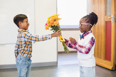 Schoolboy giving a bunch of flowers to a girl Stock Images