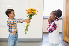 Schoolboy giving a bunch of flowers to a girl Stock Photos