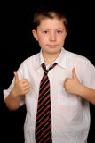 Schoolboy giving thumbs up. Smart young schoolboy giving thumbs up sign, black background Stock Images