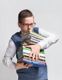 Schoolboy in glasses with books. The cute smart schoolboy teenager in a glasses bears a heavy stack of books Royalty Free Stock Images