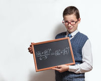 Schoolboy in glasses with mathematical equation. The cute smart schoolboy teenager in a glasses shows the black chalkboard with the mathematical equation stock image
