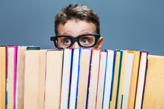 Schoolboy in glasses peeking from behind the books Stock Image