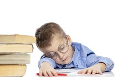 Schoolboy in glasses sleeps on the books for doing homework. Close-up. Isolated on a white background royalty free stock images