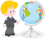 Schoolboy and globe. Elementary school student points to a country on a big globe Royalty Free Stock Photo