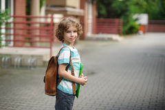 Schoolboy goes to school with a satchel behind shoulders. Stock Image