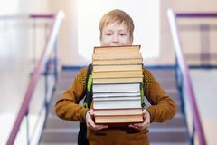 A schoolboy is going downstairs with books in his hands. A pupil with a schoolbag behind his back is going downstairs keeping a pile with of many books in his royalty free stock photo