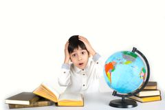 Schoolboy has got a stress from a large number of information. The boy sits at a table with textbooks and the globe. He studies the globe and reads the book. He stock photography
