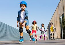 Schoolboy in helmet rollerblading with his friends Stock Photography