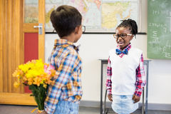 Schoolboy hiding flower behind his back in classroom Royalty Free Stock Images