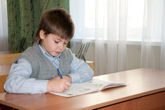 Schoolboy at his desk in the classroom Royalty Free Stock Image