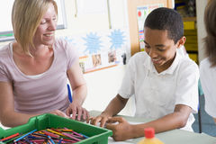 A schoolboy and his teacher in an art class Stock Image