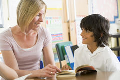 A schoolboy and his teacher reading in clas Stock Images