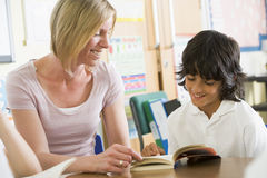 A schoolboy and his teacher reading in class Stock Photography