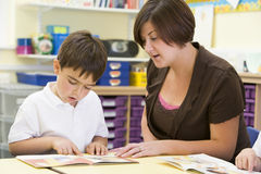 A schoolboy and his teacher reading in class Royalty Free Stock Image
