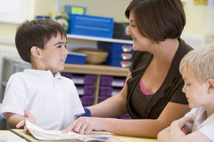 A schoolboy and his teacher reading in class Royalty Free Stock Photography