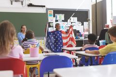 Schoolboy holding an american flag in classroom stock photos