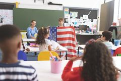 Schoolboy holding an american flag in classroom stock images