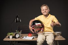 schoolboy holding american football helmet doing thumb up gesture and sitting on table with books eyeglasses plant lamp