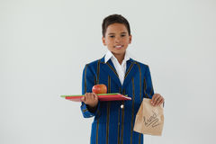 Schoolboy holding apple, books and disposable lunch bag against white background. Portrait of schoolboy holding apple, books and disposable lunch bag against Stock Image