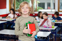 Schoolboy Holding Books With Classmates In Stock Images