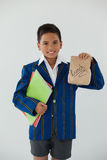 Schoolboy holding books and disposable lunch bag against white background. Portrait of schoolboy holding books and disposable lunch bag against white background Stock Image