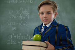 Schoolboy holding books stack with apple against chalkboard Royalty Free Stock Image