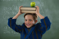 Schoolboy holding books stack with apple on head against chalkboard. Portrait of schoolboy holding books stack with apple on head against chalkboard Stock Photography