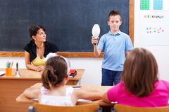 Schoolboy holding bulb in front of class Royalty Free Stock Photo