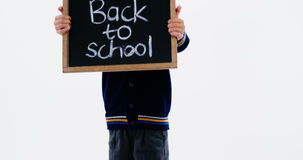 Schoolboy holding chalkboard with back to school text stock footage