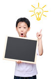 Schoolboy holding chalkboard with light bulbs Royalty Free Stock Photography