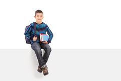 Schoolboy holding a couple of books seated on panel Stock Photos