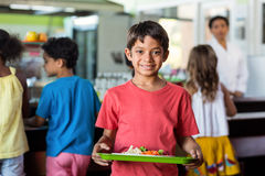 Schoolboy holding food tray in canteen. Portrait of smiling schoolboy holding food tray in canteen against classmates stock photography