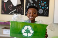 Schoolboy holding a green crate with a white recycling logo on it