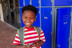 Schoolboy holding mobile phone in the locker room royalty free stock images
