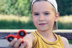 Schoolboy holding popular fidget spinner toy - close up portrait. Happy smiling child playing with Spinner. Young schoolboy holding popular fidget spinner toy stock photo