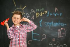 A schoolboy holding a red airplane in the hands of a training board royalty free stock photos
