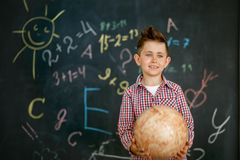 A schoolboy holding a round globe in the hands of a chalkboard painted with a chalkboard stock image