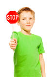 Schoolboy holding small red Stop sign icon. Close-up portrait of young fair-haired boy in green tee, holding small red Stop sign, isolated on white stock photo