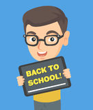 Schoolboy holding tablet with text back to school. Happy little caucasian schoolboy in glasses holding a tablet computer with text back to school. Cheerful Royalty Free Stock Photo