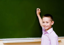 Schoolboy holding a white chalk about to write Royalty Free Stock Photos
