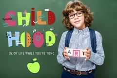 Schoolboy holding wooden cubes with word art near blackboard with childhood lettering stock image