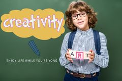 Schoolboy holding wooden cubes with word art near blackboard. With creativity lettering royalty free stock photography