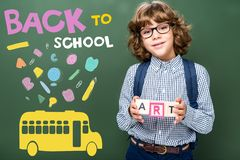 Schoolboy holding wooden cubes with word art near blackboard with icons bus and back to. School lettering stock photos