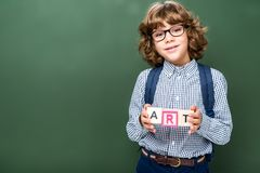 Schoolboy holding wooden cubes with word art. Near blackboard stock image