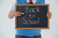 Schoolboy holding writing slate with text back to school against white background Stock Photos