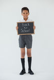 Schoolboy holding writing slate with text back to school against white background Stock Photography